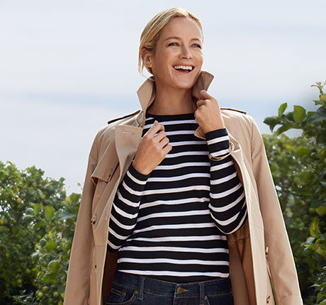 Woman in striped shirt with tan trench coat draped over shoulders