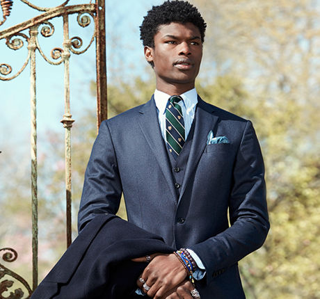 Man models navy three-piece suit & striped tie