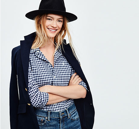 Woman wears navy gingham checked shirt & black brimmed hat