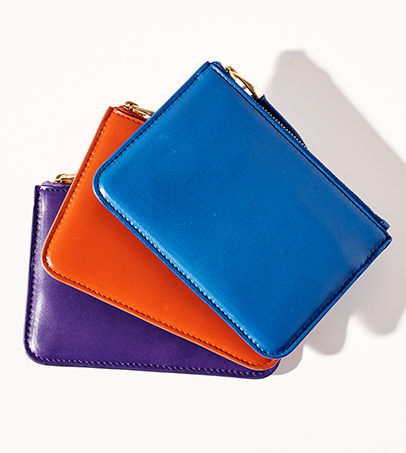 "Purple, orange & blue leather zip pouches with ""RL"" debossed at front"
