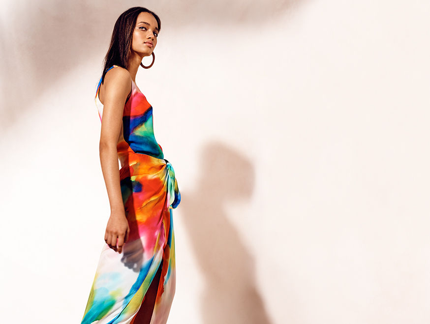 Woman models sleeveless wrap dress with painterly, rainbow-hued print