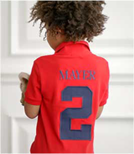 Boy wears red Polo shirt with his name embroidered across the back