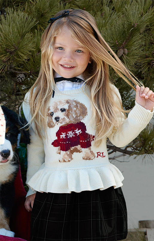 Girl wears peplum sweater with intarsia-knit puppy