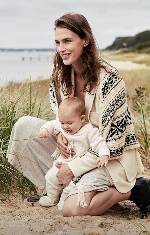 Woman wearing geometric-patterned shawl & monochrome  outfit holds baby