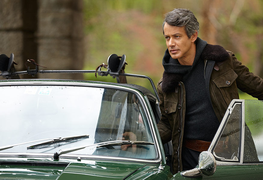Andrew Lauren, wearing olive suede jacket layered over charcoal hoodie, gets into green vintage sports car