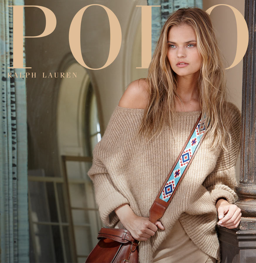 Woman wearing oversized beige sweater and carrying leather bag with embroidered cross-body strap leans against pillar