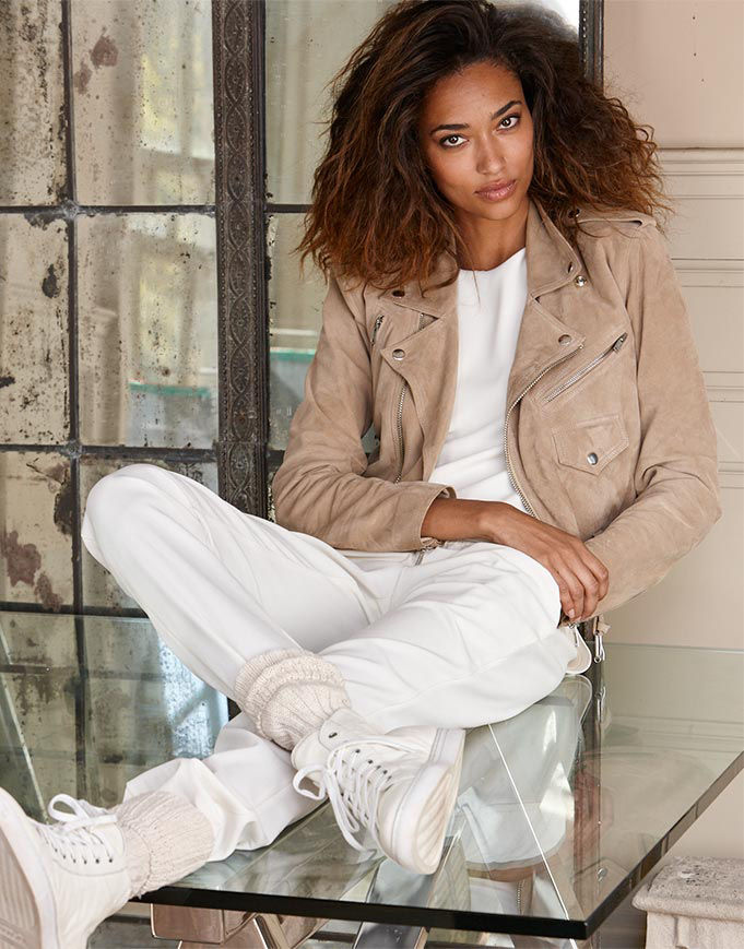 Woman sitting on glass-top table layers tan suede moto jacket over white top, jogger pant & sneakers