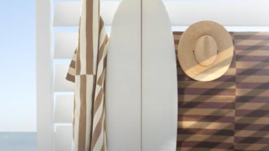 White surfboard leans against wall where straw hat & two beach towels with off-set stripes hang