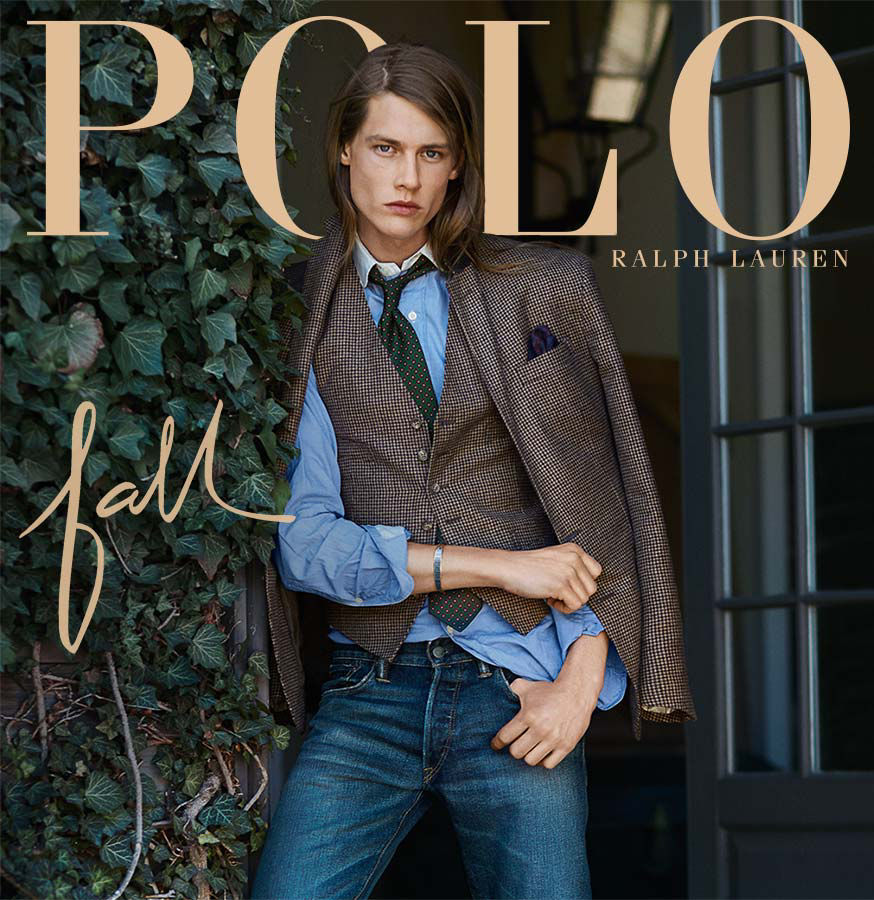 Fall preview: Man wears brown blazer & vest over blue dress shirt & jeans.