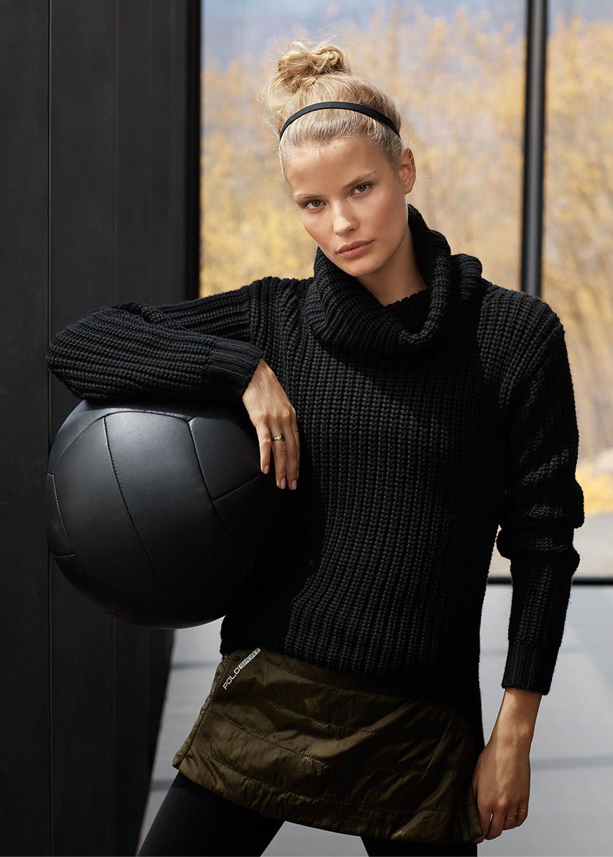 Woman in black chunky-knit sweater stands with black medicine ball