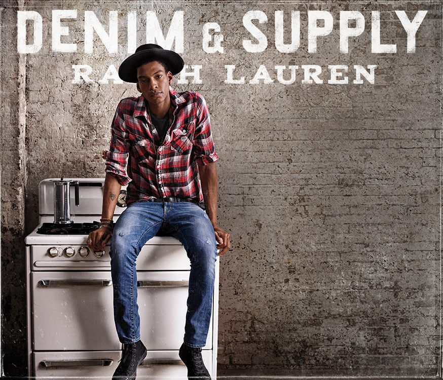 Denim & Supply Ralph Lauren. Man wearing brimmed hat, plaid shirt & jeans sits on white stove