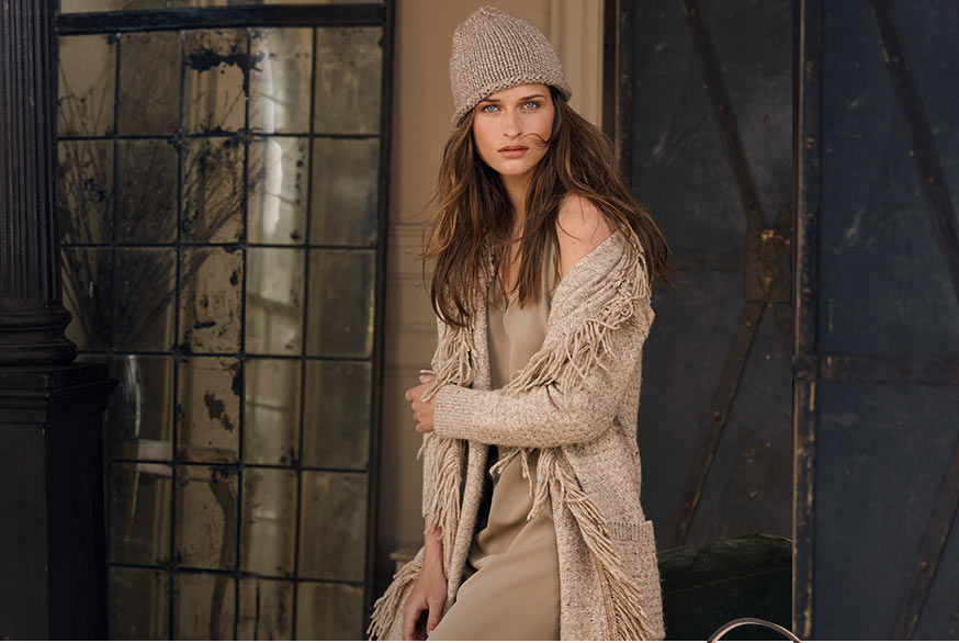 Woman models knit cap, fringed sweater coat & sleeveless dress, all in shades of taupe