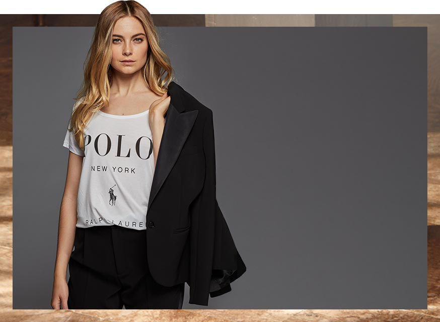 "Woman in tee with ""Polo New York"" text carries blazer over shoulder"