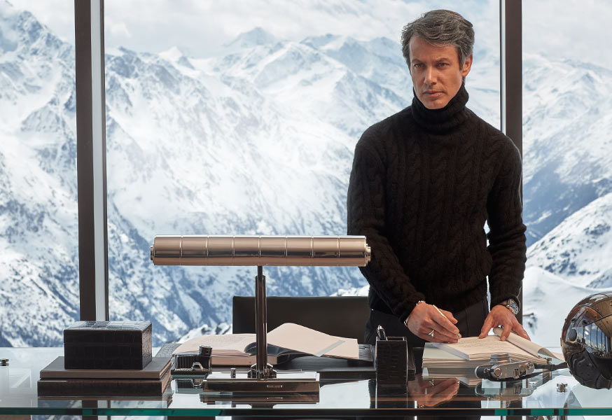 Andrew Lauren, wearing cable-knit turtleneck, stands at desk with sleek accessories