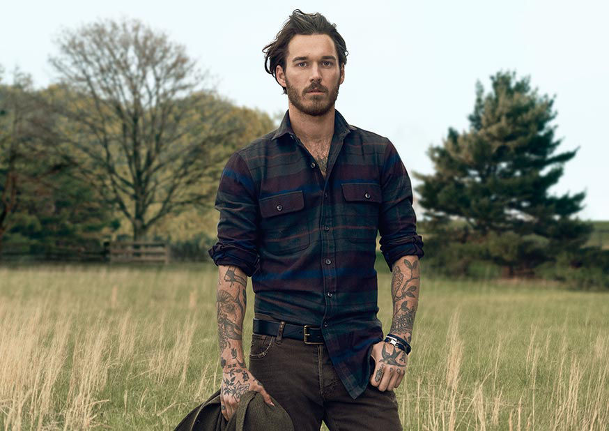 Man models plaid flannel button-down shirt