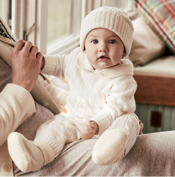 Ralph Lauren Baby Logo Baby wearing cream cable-knit hat \u0026amp; coverall sits on woman\u0026#39;s lap