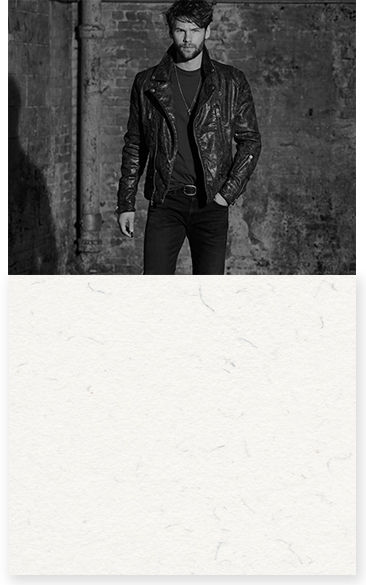 Greyscale image of man in leather jacket, T-shirt & jeans