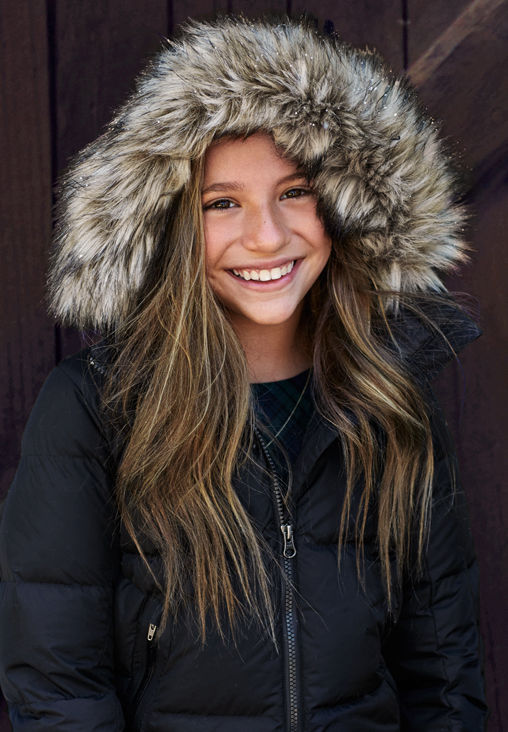 Girl wears puffer jacket with faux-fur-trimmed hood