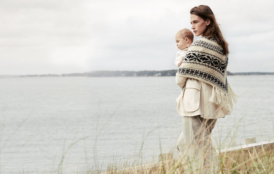 Woman in geometric-patterned shawl holds baby in cream outfit