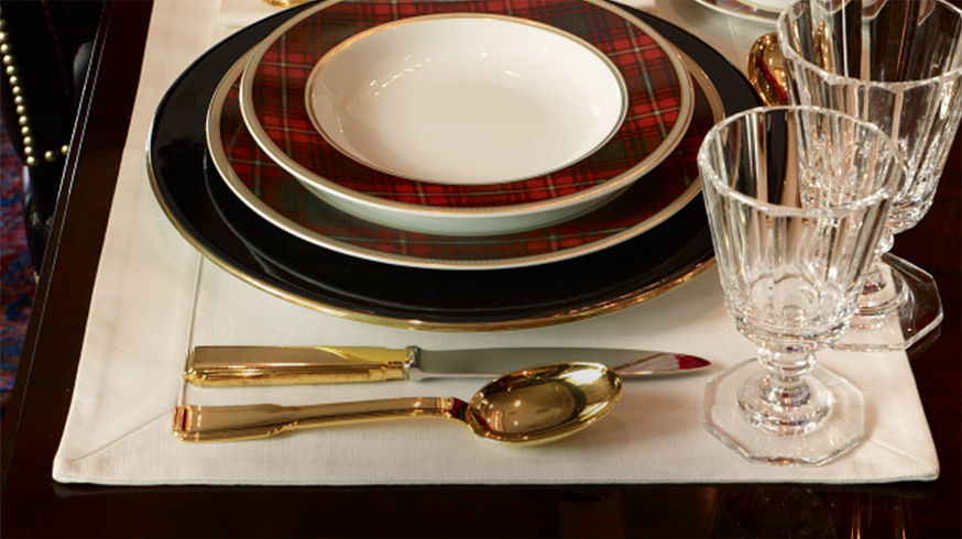 Place-setting with gold-toned flatware, plaid-patterned dishes & stemmed glasses