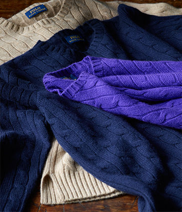 Pile of cable-knit sweaters in purple, navy & taupe