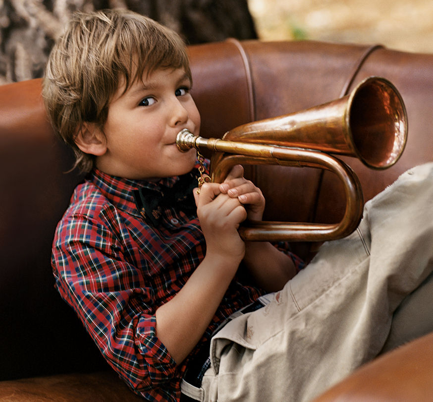 Boy in red plaid shirt & chinos plays a horn