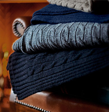 Haphazard stack of cable-knit sweaters in navy, grey, blue & taupe