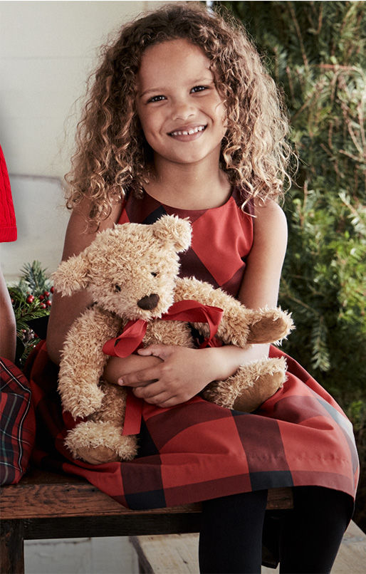 Girl wears red plaid sleeveless dress & holds teddy bear