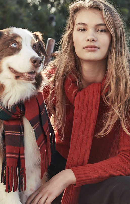 Woman in cable-knit sweater & scarf sits with dog wearing plaid scarf
