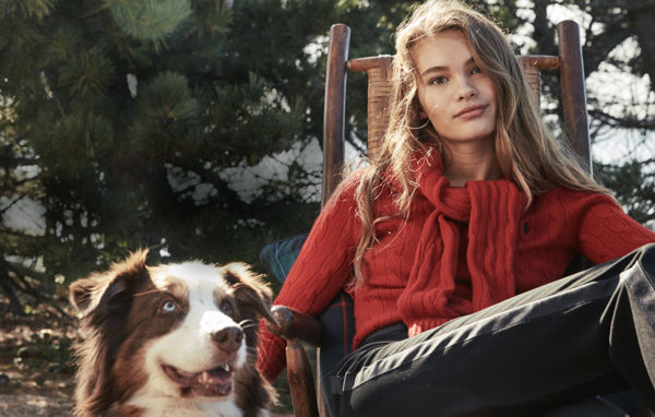 Woman in red cable-knit sweater \u0026amp; black pant sits with dog