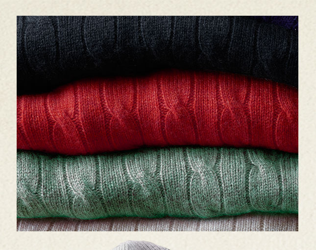 Stack of cable-knit sweaters in black, red, light green & white