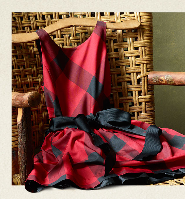 Red plaid sleeveless dress draped over a rattan chair