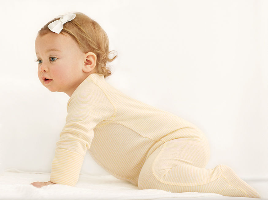 Baby girl crawls while wearing yellow striped onesie.