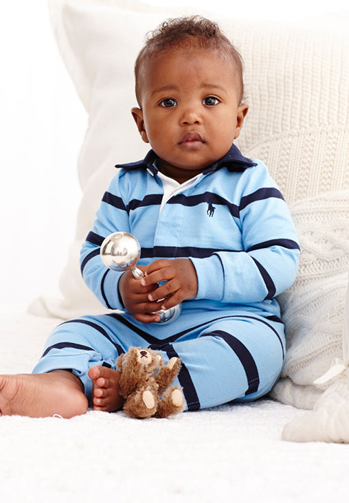 baby boy wears blue striped one-piece and holds silver rattle.
