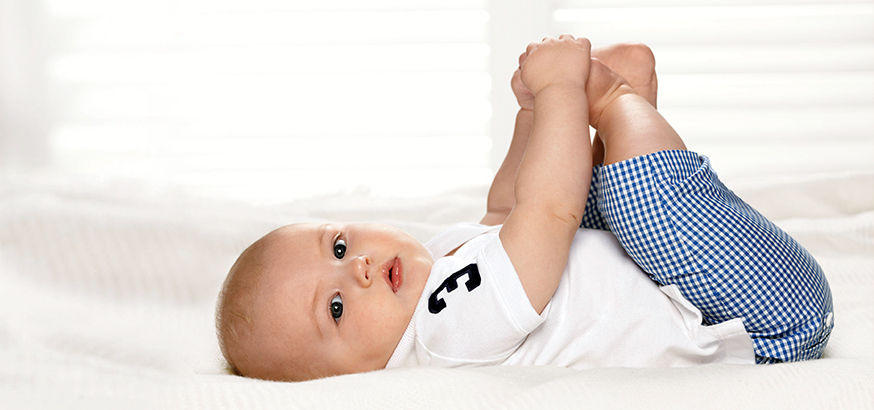 Baby wears white Polo shirt and blue checked pants.