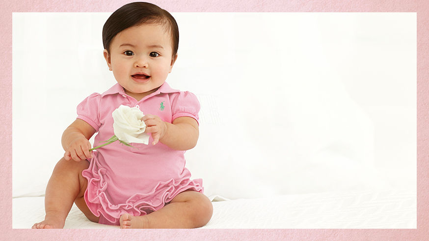 Baby girl wears pink Polo dress and holds white rose.