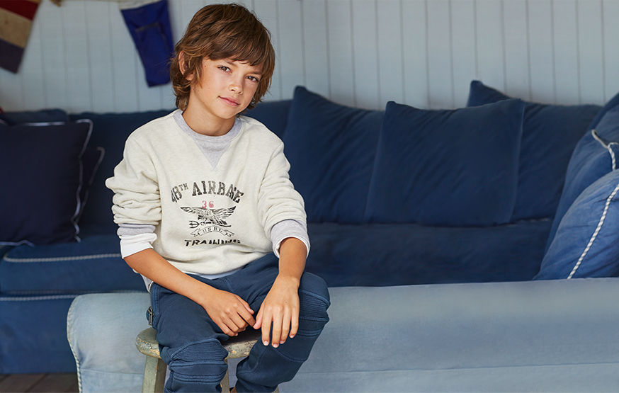 Boy sitting on stool wears off-white graphic sweatshirt and grey sweatpants.