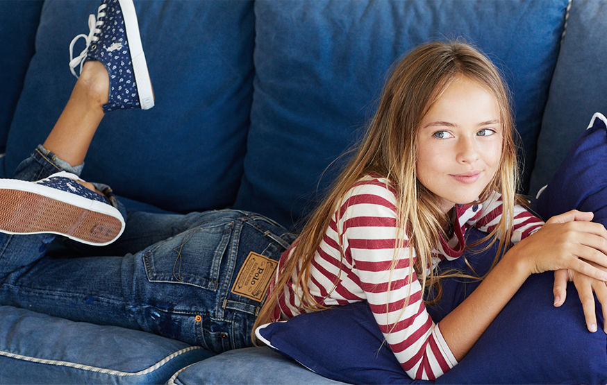 Girl lies on couch wearing jeans and red-and-white striped long-sleeve tee.