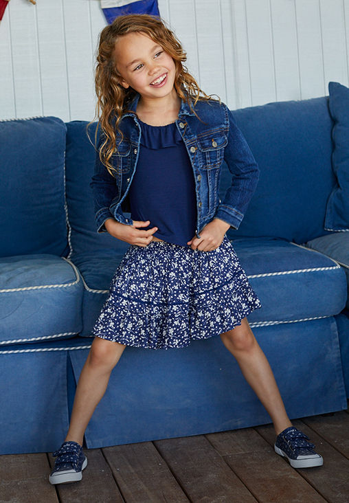 Girl wears floral ruffled skirt, navy top, and denim jacket.