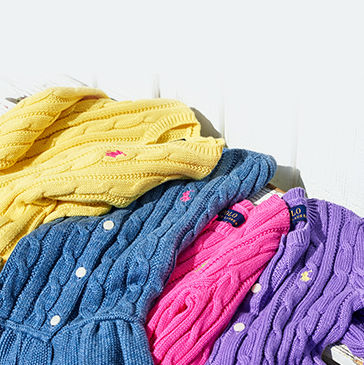 Array of colorful cable-knit sweaters in yellow, blue, pink, and purple.