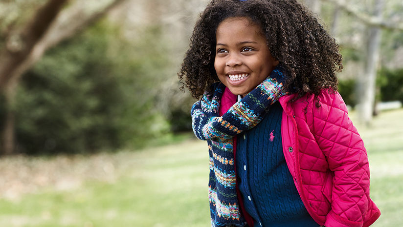 Girl layers pink down coat, navy cable cardigan, and patterned scarf.