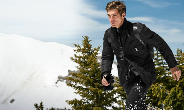 Man in all black walks in front of pine trees \u0026amp; snowy mountains. Polo Ralph Lauren Logo