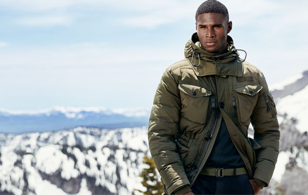 Man in olive-hued utility jacket stands in front of snowy mountains. Polo Ralph Lauren Logo