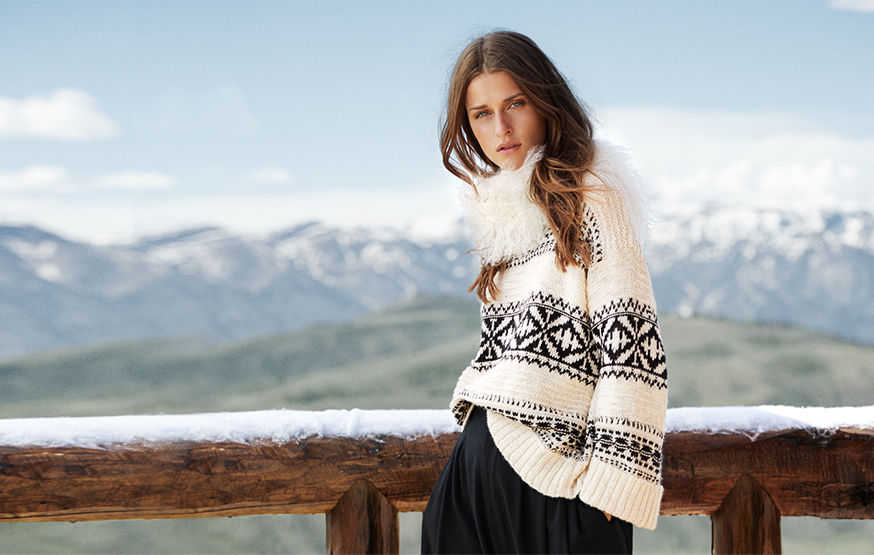 Woman in geometric-patterned cream-and-white sweater stands in wintry scene