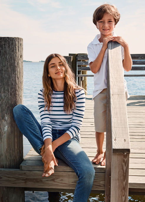 Woman in striped shirt & boy in white Polo shirt relax on dock