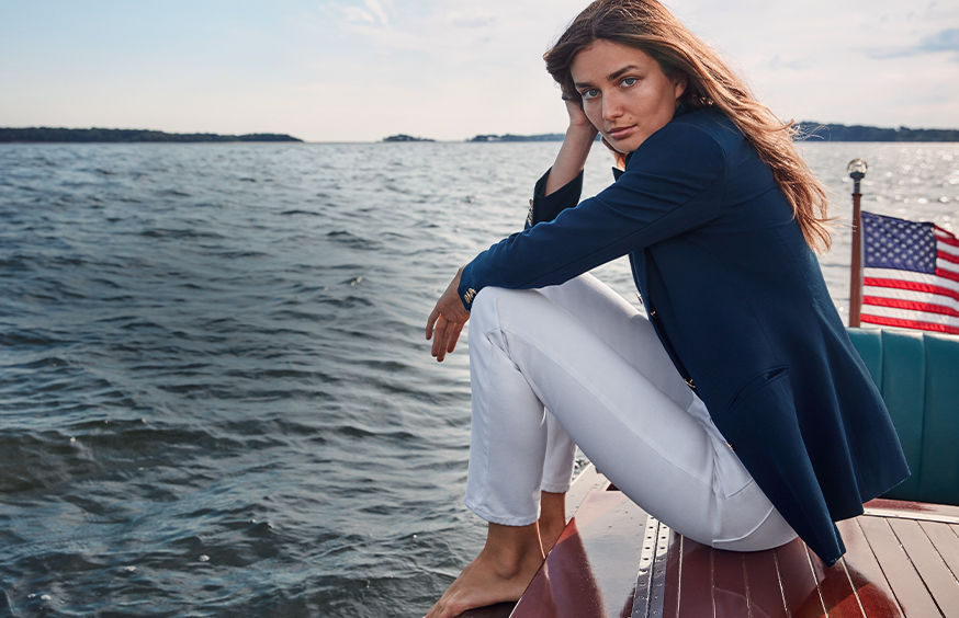 Woman in navy blazer & white jeans sits on boat