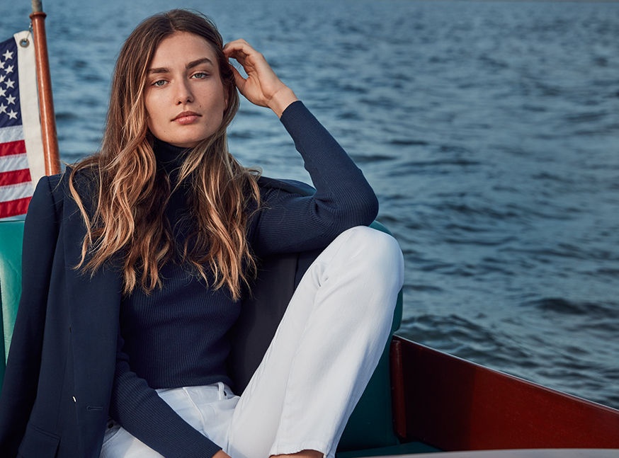 Woman on boat wearing navy blazer & turtleneck paired with white pants