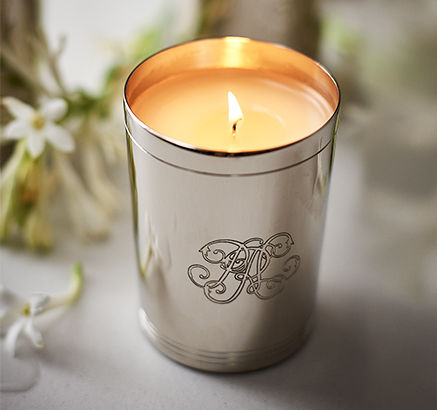 Lit candle in a metal holder with RL monogram