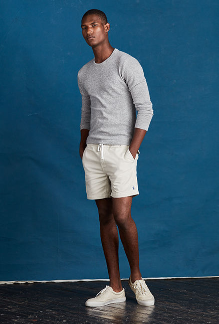 Man in light grey cashmere crewneck sweater & white shorts