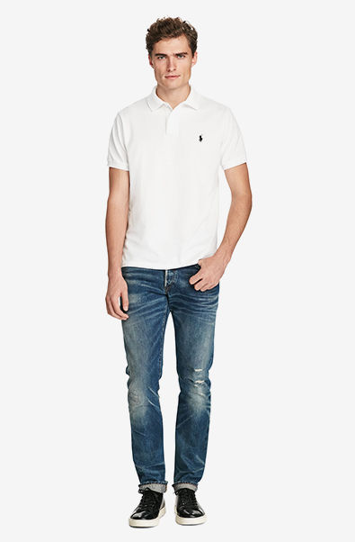 Man in white Polo shirt, distressed jeans & black leather sneakers